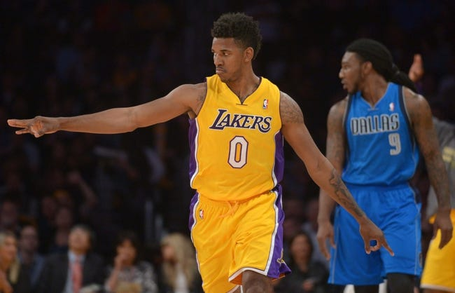 Apr 4, 2014; Los Angeles, CA, USA; Los Angeles Lakers guard Nick Young (0) reacts after a 3-point basket as Dallas Mavericks forward Jae Crowder (9) watches at Staples Center. Mandatory Credit: Kirby Lee-USA TODAY Sports