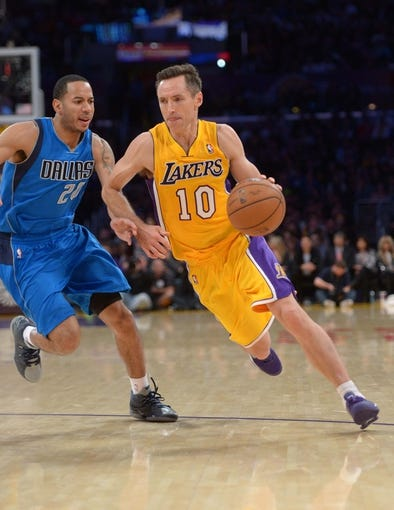 Apr 4, 2014; Los Angeles, CA, USA; Los Angeles Lakers guard Steve Nash (10) is defended by Dallas Mavericks guard Devin Harris (20) at Staples Center. The Mavericks defeated the Lakers 107-95.  Mandatory Credit: Kirby Lee-USA TODAY Sports