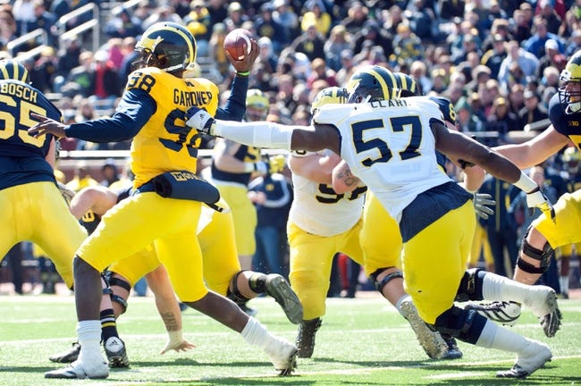 Apr 5, 2014; Ann Arbor, MI, USA; Michigan Wolverines defensive end Frank Clark (57) pressures quarterback Devin Gardner (98) during the Spring Game at Michigan Stadium. Mandatory Credit: Tim Fuller-USA TODAY Sports