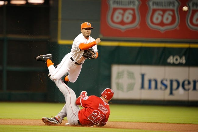 Apr 5, 2014; Houston, TX, USA; Houston Astros second baseman Jose Altuve (27) throws over a sliding Los Angeles Angels center fielder Mike Trout (27) for a double play during the first inning at Minute Maid Park. Mandatory Credit: Andrew Richardson-USA TODAY Sports