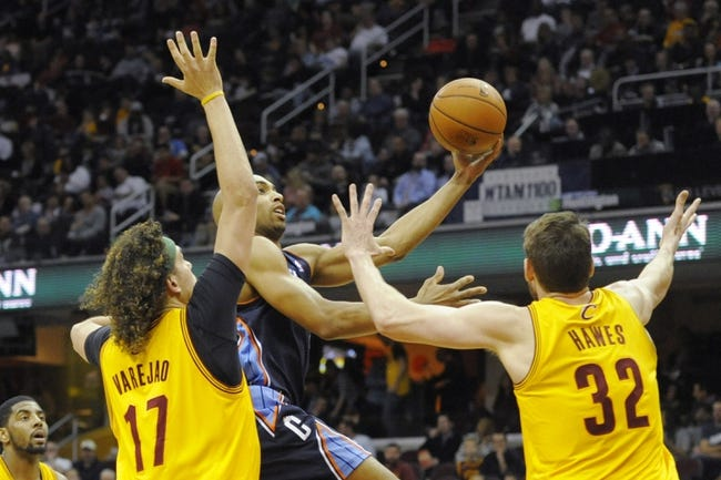 Apr 5, 2014; Cleveland, OH, USA;Charlotte Bobcats guard Gerald Henderson (center) drives between Cleveland Cavaliers center Anderson Varejao (17) and center Spencer Hawes (32) in the second quarter at Quicken Loans Arena. Mandatory Credit: David Richard-USA TODAY Sports