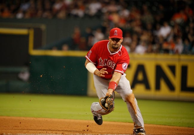 Apr 5, 2014; Houston, TX, USA; Los Angeles Angels first baseman Albert Pujols (5) fields a ground ball during the eighth inning against the Houston Astros at Minute Maid Park. Mandatory Credit: Andrew Richardson-USA TODAY Sports