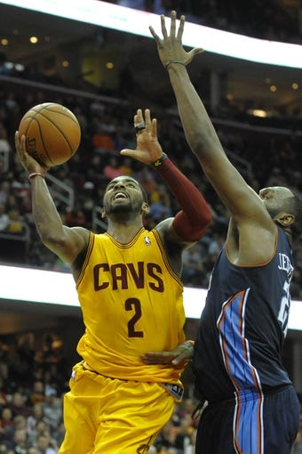 Apr 5, 2014; Cleveland, OH, USA; Cleveland Cavaliers guard Kyrie Irving (2) drives against Charlotte Bobcats center Al Jefferson (25) in the fourth quarter at Quicken Loans Arena. Mandatory Credit: David Richard-USA TODAY Sports