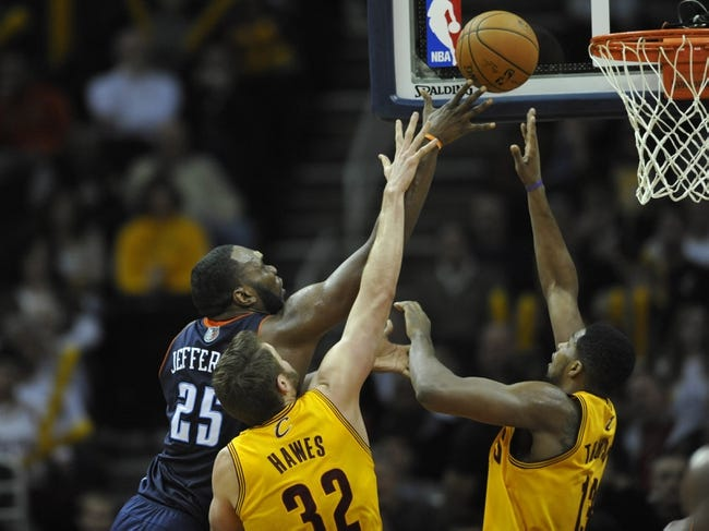 Apr 5, 2014; Cleveland, OH, USA; Charlotte Bobcats center Al Jefferson (25) shoots the ball in front of Cleveland Cavaliers center Spencer Hawes (32) and forward Tristan Thompson (13) in the third quarter at Quicken Loans Arena. Mandatory Credit: David Richard-USA TODAY Sports