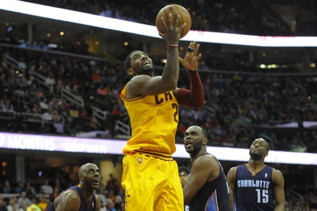 Apr 5, 2014; Cleveland, OH, USA; Cleveland Cavaliers guard Kyrie Irving (2) shoots the ball against the Charlotte Bobcats defense in the fourth quarter at Quicken Loans Arena. Mandatory Credit: David Richard-USA TODAY Sports