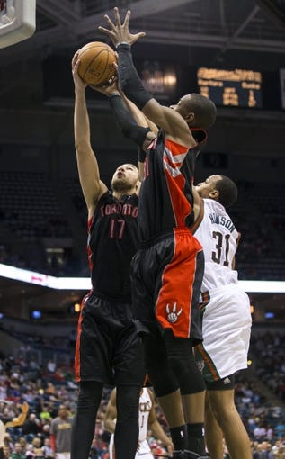 Apr 5, 2014; Milwaukee, WI, USA; Toronto Raptors center Jonas Valanciunas (17) and Terrence Ross (31) reach for a rebound during the fourth quarter against the Milwaukee Bucks at BMO Harris Bradley Center.  The Raptors won 102-98.  Mandatory Credit: Jeff Hanisch-USA TODAY Sports