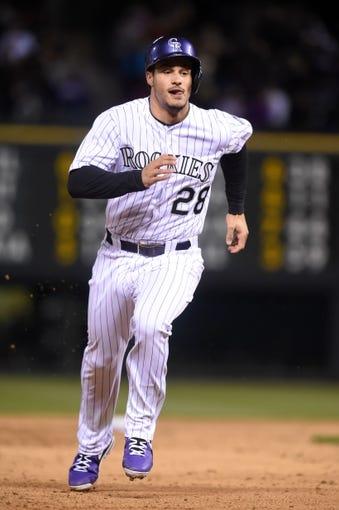 Apr 5, 2014; Denver, CO, USA; Colorado Rockies third baseman Nolan Arenado (28) heads to third base in the eighth inning against the Arizona Diamondbacks at Coors Field. The Rockies defeated the Diamondbacks 9-4. Mandatory Credit: Ron Chenoy-USA TODAY Sports