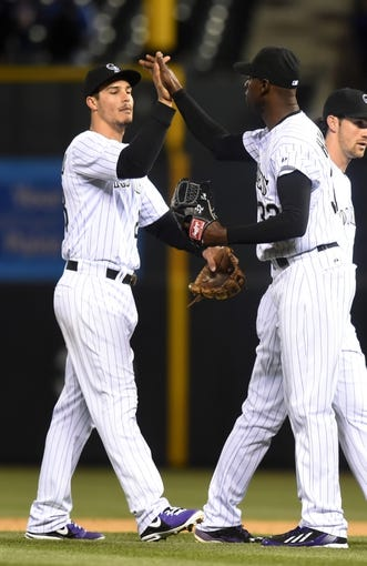 Apr 5, 2014; Denver, CO, USA; Colorado Rockies relief pitcher LaTroy Hawkins (32) (right) and third baseman Nolan Arenado (28) (left) high five each other following the win against the Arizona Diamondbacks at Coors Field. The Rockies defeated the Diamondbacks 9-4. Mandatory Credit: Ron Chenoy-USA TODAY Sports