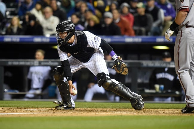 Apr 5, 2014; Denver, CO, USA; Colorado Rockies catcher Jordan Pacheco (58) controls a foul tip in the sixth inning against the Arizona Diamondbacks at Coors Field. The Rockies defeated the Diamondbacks 9-4. Mandatory Credit: Ron Chenoy-USA TODAY Sports