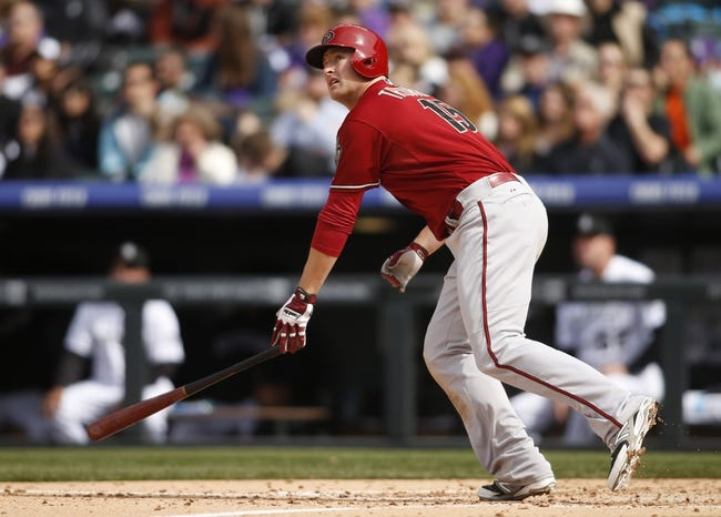 Apr 6, 2014; Denver, CO, USA; Arizona Diamondbacks left fielder Mark Trumbo (15) hits a home run during the fifth inning against the Colorado Rockies at Coors Field. Mandatory Credit: Chris Humphreys-USA TODAY Sports