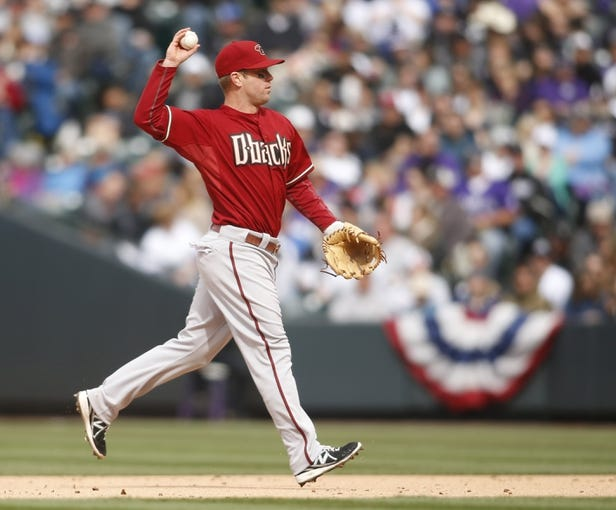 Apr 6, 2014; Denver, CO, USA; Arizona Diamondbacks second baseman Aaron Hill (2) fields a ground ball during the sixth inning against the Colorado Rockies at Coors Field. Mandatory Credit: Chris Humphreys-USA TODAY Sports