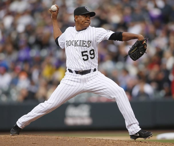 Apr 6, 2014; Denver, CO, USA; Colorado Rockies pitcher Wilton Lopez (59) delivers a pitch during the seventh inning against the Arizona Diamondbacks at Coors Field. Mandatory Credit: Chris Humphreys-USA TODAY Sports