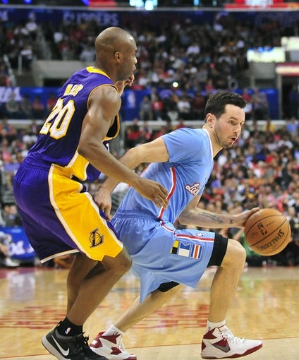 April 6, 2014; Los Angeles, CA, USA; Los Angeles Clippers guard J.J. Redick (4) controls the ball against Los Angeles Lakers guard Jodie Meeks (20) during the second half at Staples Center. Mandatory Credit: Gary A. Vasquez-USA TODAY Sports