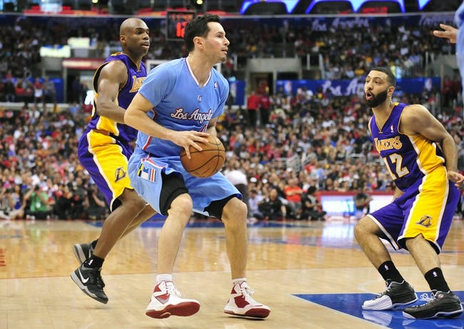 April 6, 2014; Los Angeles, CA, USA; Los Angeles Clippers guard J.J. Redick (4) controls the ball against Los Angeles Lakers guard Jodie Meeks (20) and guard Kendall Marshall (12) during the second half at Staples Center. Mandatory Credit: Gary A. Vasquez-USA TODAY Sports