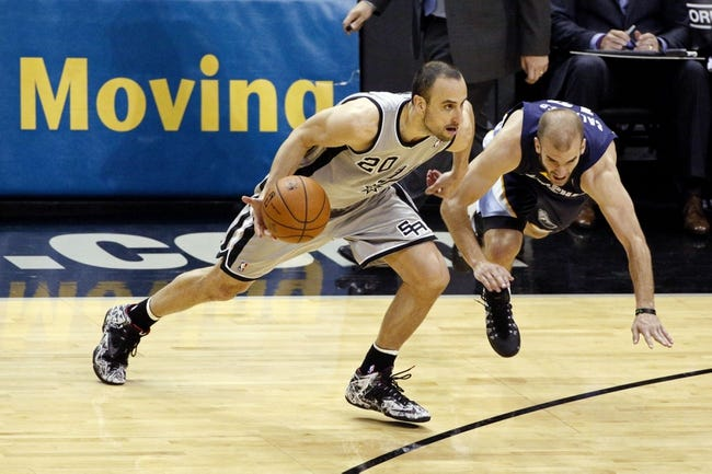 Apr 6, 2014; San Antonio, TX, USA; San Antonio Spurs guard Manu Ginobili (20) drives to the basket past Memphis Grizzlies guard Nick Calathes (right) during the second half at AT&T Center. The Spurs won 112-92. Mandatory Credit: Soobum Im-USA TODAY Sports