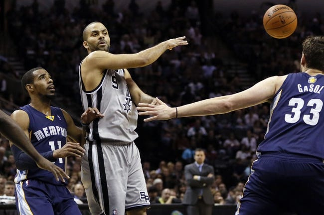 Apr 6, 2014; San Antonio, TX, USA; San Antonio Spurs guard Tony Parker (9) passes the bass as Memphis Grizzlies guard Mike Conley (11) defends during the second half at AT&T Center. Mandatory Credit: Soobum Im-USA TODAY Sports