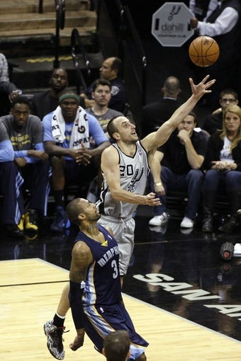 Apr 6, 2014; San Antonio, TX, USA; San Antonio Spurs guard Manu Ginobili (20) shoots the ball past Memphis Grizzlies forward James Johnson (3) during the second half at AT&T Center. The Spurs won 112-92. Mandatory Credit: Soobum Im-USA TODAY Sports