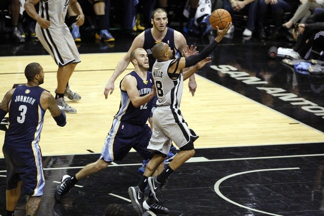 Apr 6, 2014; San Antonio, TX, USA; San Antonio Spurs guard Patrick Mills (8) drives to the basket past Memphis Grizzlies guard Nick Calathes (12) during the second half at AT&T Center. The Spurs won 112-92. Mandatory Credit: Soobum Im-USA TODAY Sports