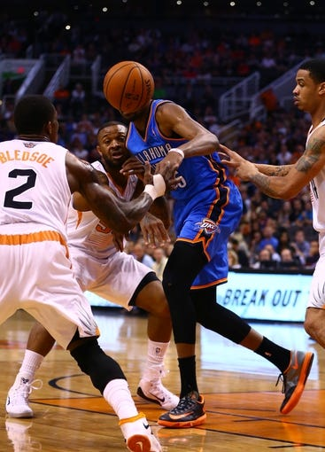 Apr 6, 2014; Phoenix, AZ, USA; Oklahoma City Thunder forward Kevin Durant (center) loses the ball against the Phoenix Suns at US Airways Center. The Suns defeated the Thunder 122-115. Mandatory Credit: Mark J. Rebilas-USA TODAY Sports