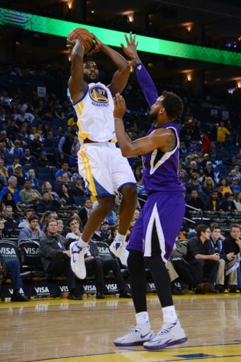 April 4, 2014; Oakland, CA, USA; Golden State Warriors forward Hilton Armstrong (57) shoots the ball against Sacramento Kings forward Derrick Williams (13) during the fourth quarter at Oracle Arena. The Warriors defeated the Kings 102-69. Mandatory Credit: Kyle Terada-USA TODAY Sports