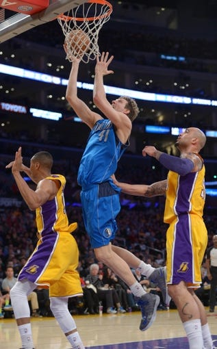Apr 4, 2014; Los Angeles, CA, USA; Dallas Mavericks forward Dirk Nowitzki (41) shoots the ball as Los Angeles Lakers forward Wesley Johnson (11) and center Robert Sacre (50) defend at Staples Center. Mandatory Credit: Kirby Lee-USA TODAY Sports