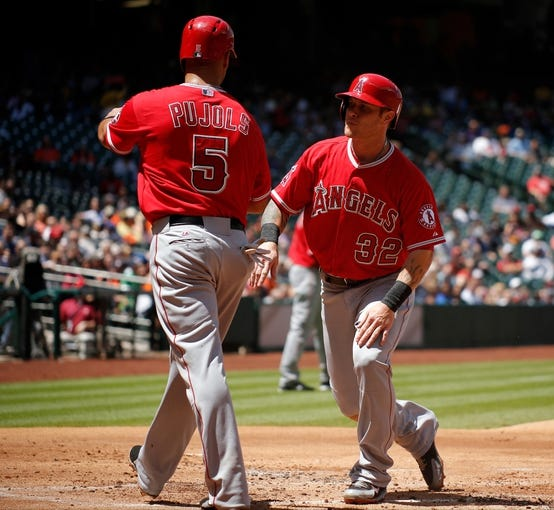 [Apr 7, 2014; Houston, TX, USA; Los Angeles Angels left fielder Josh Hamilton (32) is greeted at the plate by first baseman Albert Pujols (5) after scoring a run during the first inning against the Houston Astros at Minute Maid Park. Mandatory Credit: Andrew Richardson-USA TODAY Sports