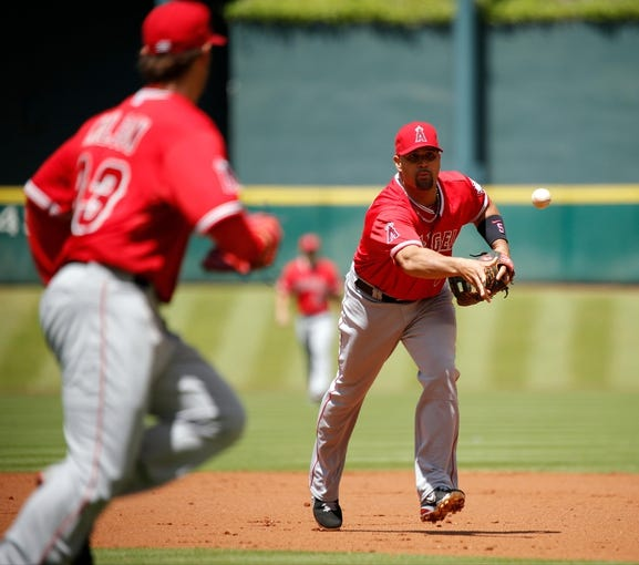 Apr 7, 2014; Houston, TX, USA; Los Angeles Angels first baseman Albert Pujols (5) tosses the ball to starting pitcher C.J. Wilson (33) during the first inning against the Houston Astros at Minute Maid Park. Mandatory Credit: Andrew Richardson-USA TODAY Sports