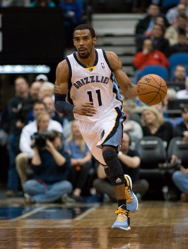 Apr 2, 2014; Minneapolis, MN, USA;  Memphis Grizzlies guard Mike Conley (11) dribbles up court in the first half against the Minnesota Timberwolves at Target Center. The Wolves defeated the Grizzlies 102-88.  Mandatory Credit: Marilyn Indahl-USA TODAY Sports