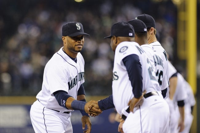 Apr 8, 2014; Seattle, WA, USA; Seattle Mariners second baseman Robinson Cano (22) shakes manager Lloyd McClendon's (23) hand during the player introductions prior to the game against the Los Angeles Angels at Safeco Field. Mandatory Credit: Steven Bisig-USA TODAY Sports