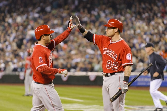Apr 8, 2014; Seattle, WA, USA; Los Angeles Angels third baseman David Freese (6) (left) and Los Angeles Angels left fielder Josh Hamilton (32) high five after Freese hit a solo home run against the Seattle Mariners during the first inning at Safeco Field. Mandatory Credit: Steven Bisig-USA TODAY Sports