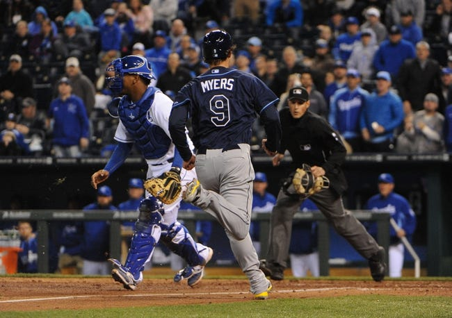 Apr 8, 2014; Kansas City, MO, USA; Tampa Bay Rays right fielder Wil Myers (9) scores on a hit by first baseman James Loney (not pictured) against Kansas City Royals catcher Salvador Perez (13) in the ninth inning at Kauffman Stadium. Mandatory Credit: John Rieger-USA TODAY Sports