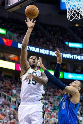 Apr 8, 2014; Salt Lake City, UT, USA; Utah Jazz center Derrick Favors (15) shoots over Dallas Mavericks forward Shawn Marion (0) during the second half at EnergySolutions Arena. The Mavericks won 95-83. Mandatory Credit: Russ Isabella-USA TODAY Sports