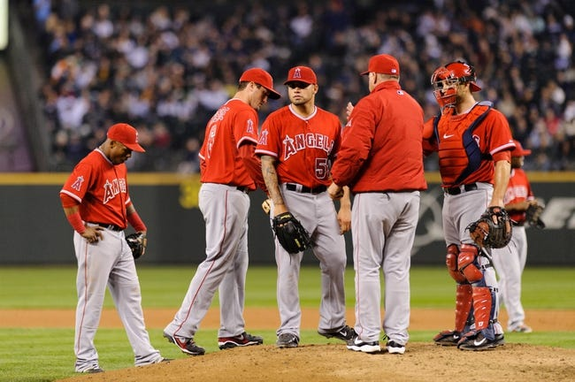 Apr 8, 2014; Seattle, WA, USA; Los Angeles Angels starting pitcher Hector Santiago (53) is pulled from the game by Los Angeles Angels manager Mike Scioscia (14) during the fifth inning against the Seattle Mariners at Safeco Field. Mandatory Credit: Steven Bisig-USA TODAY Sports