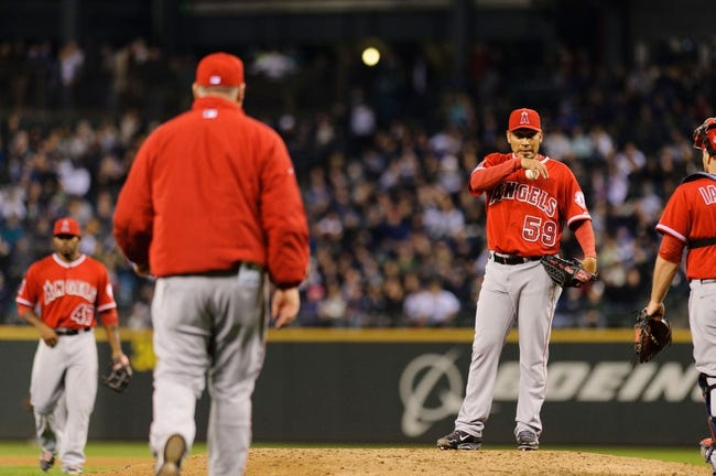 Apr 8, 2014; Seattle, WA, USA; Los Angeles Angels relief pitcher Fernando Salas (59) is pulled from the game by Los Angeles Angels manager Mike Scioscia (14) during the seventh inning against the Seattle Mariners at Safeco Field. Mandatory Credit: Steven Bisig-USA TODAY Sports