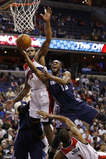 Apr 9, 2014; Washington, DC, USA; Charlotte Bobcats guard Kemba Walker (15) shoots the ball as Washington Wizards forward Trevor Booker (35) and Wizards forward Trevor Ariza (1) defend in the fourth quarter at Verizon Center. The Bobcats won 94-88 in overtime. Mandatory Credit: Geoff Burke-USA TODAY Sports