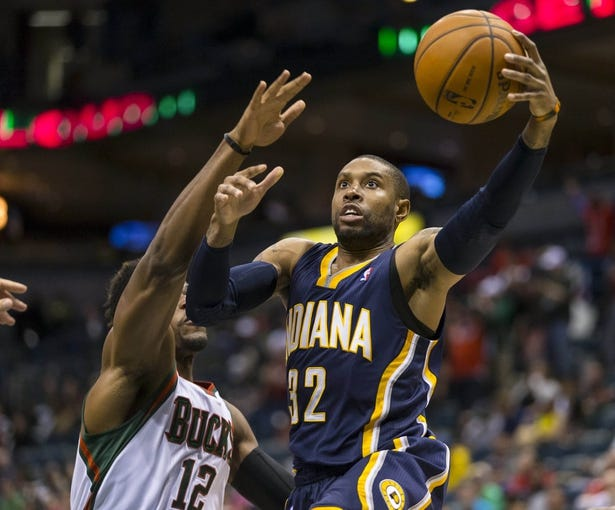 Apr 9, 2014; Milwaukee, WI, USA; Indiana Pacers guard C.J. Watson (32) shoots the ball around Milwaukee Bucks forward Jeff Adrien (12) during the fourth quarter at BMO Harris Bradley Center. The Pacers won 104-102.  Mandatory Credit: Jeff Hanisch-USA TODAY Sports