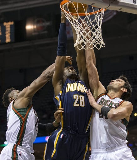 Apr 9, 2014; Milwaukee, WI, USA; Indiana Pacers center Ian Mahinmi (28) shoots the ball between Milwaukee Bucks forward Jeff Adrien (12) and center Zaza Pachulia (27) during the fourth quarter at BMO Harris Bradley Center.  The Pacers won 104-102.  Mandatory Credit: Jeff Hanisch-USA TODAY Sports