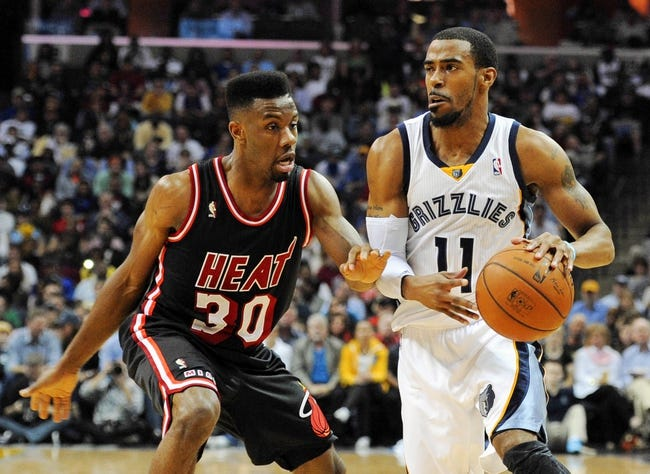 Apr 9, 2014; Memphis, TN, USA; Memphis Grizzlies guard Mike Conley (11) handles the ball against Miami Heat guard Norris Cole (30) during the game at FedExForum. Memphis Grizzlies beat the Miami Heat 107 - 102. Mandatory Credit: Justin Ford-USA TODAY Sports
