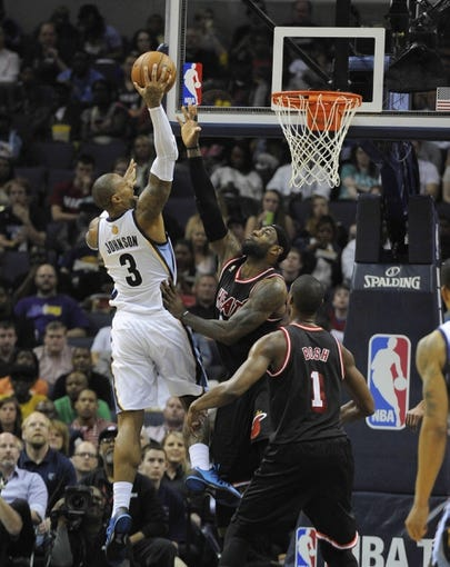Apr 9, 2014; Memphis, TN, USA; Memphis Grizzlies forward James Johnson (3) shoots over Miami Heat forward LeBron James (6) during the game at FedExForum. Memphis Grizzlies beat the Miami Heat 107 - 102. Mandatory Credit: Justin Ford-USA TODAY Sports