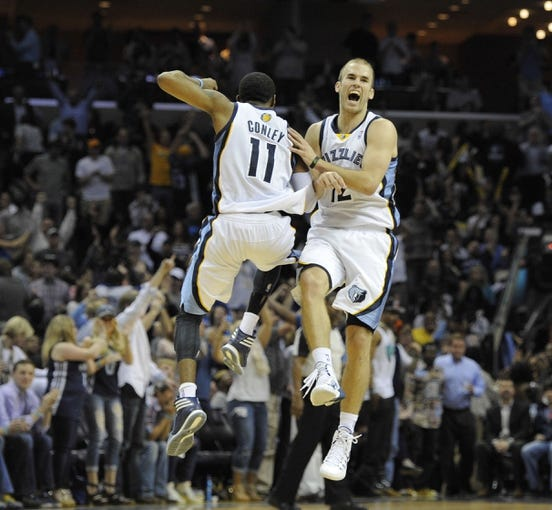 Apr 9, 2014; Memphis, TN, USA; Memphis Grizzlies guard Nick Calathes (12) and guard Mike Conley (11) celebrate during the game against the Miami Heat at FedExForum. Memphis Grizzlies beat the Miami Heat 107 - 102. Mandatory Credit: Justin Ford-USA TODAY Sports