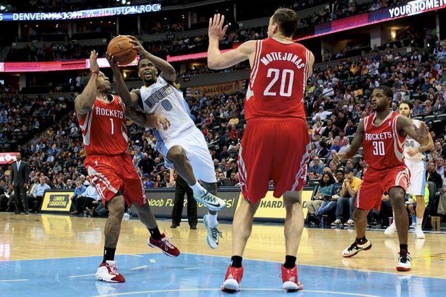 Apr 9, 2014; Denver, CO, USA; Denver Nuggets point guard Aaron Brooks (0) drives to the net against Houston Rockets point guard Isaiah Canaan (1) and power forward Donatas Motiejunas (20) in the fourth quarter at the Pepsi Center. The Nuggets won 123-116. Mandatory Credit: Isaiah J. Downing-USA TODAY Sports