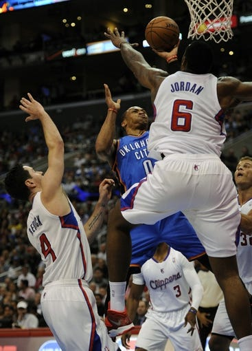 Apr 9, 2014; Los Angeles, CA, USA; Oklahoma City Thunder guard Russell Westbrook (0) shoots the ball as Los Angeles Clippers center DeAndre Jordan (R) and Los Angeles Clippers guard J.J. Reddick (L) defend during the first quarter at Staples Center. Mandatory Credit: Kelvin Kuo-USA TODAY Sports