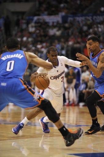 Apr 9, 2014; Los Angeles, CA, USA; Los Angeles Clippers guard Chris Paul (3) dribbles the ball between Oklahoma City Thunder guard Thabo Sefolosha (R) and guard Russell Westbrook (L) during the fourth quarter at Staples Center. The Thunder won 107-101. Mandatory Credit: Kelvin Kuo-USA TODAY Sports