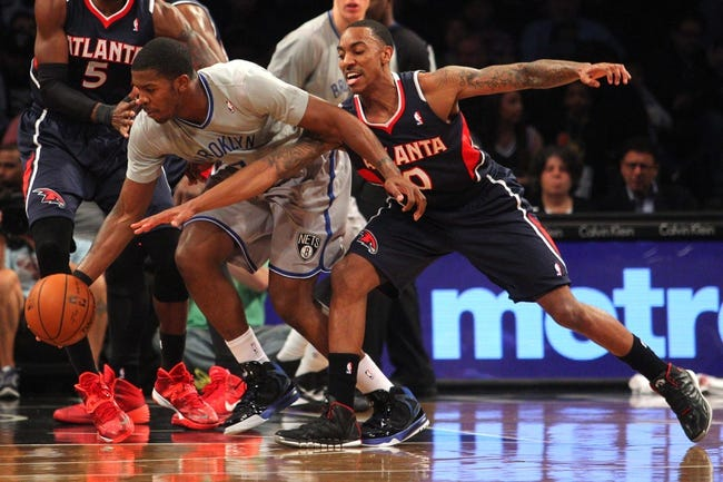 Apr 11, 2014; Brooklyn, NY, USA; Atlanta Hawks point guard Jeff Teague (0) attempts to steal the ball from Brooklyn Nets shooting guard Joe Johnson (7) during the first quarter of a game at Barclays Center. Mandatory Credit: Brad Penner-USA TODAY Sports