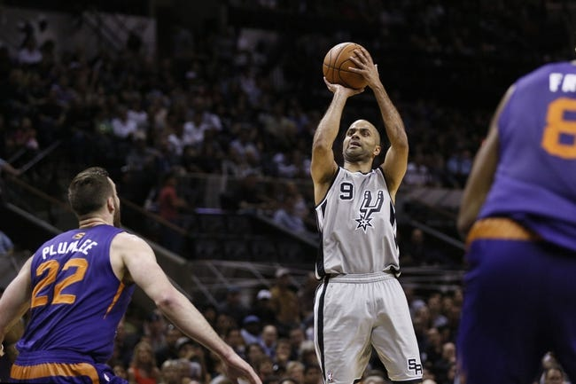 Apr 11, 2014; San Antonio, TX, USA; San Antonio Spurs guard Tony Parker (9) shoots the ball as Phoenix Suns  center Miles Plumlee (22) looks on during the first half at AT&T Center. Mandatory Credit: Soobum Im-USA TODAY Sports