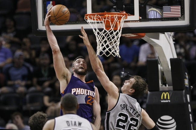 Apr 11, 2014; San Antonio, TX, USA; Phoenix Suns  center Miles Plumlee (22) attempts to dunk the ball as San Antonio Spurs forward Tiago Splitter (22) defends during the first half at AT&T Center. Mandatory Credit: Soobum Im-USA TODAY Sports