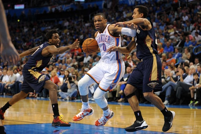 Apr 11, 2014; Oklahoma City, OK, USA;  Oklahoma City Thunder guard Russell Westbrook (0) drives to the basket against New Orleans Pelicans guard Brian Roberts (22) and New Orleans Pelicans forward Al-Farouq Aminu (0) during the second quarter at Chesapeake Energy Arena. Mandatory Credit: Mark D. Smith-USA TODAY Sports