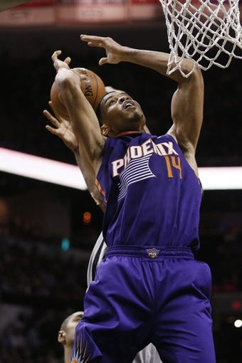 Apr 11, 2014; San Antonio, TX, USA; Phoenix Suns  guard Gerald Green (14) gets fouled while shooting against San Antonio Spurs forward Kawhi Leonard (behind) during the second half at AT&T Center. The Spurs won 112-104. Mandatory Credit: Soobum Im-USA TODAY Sports