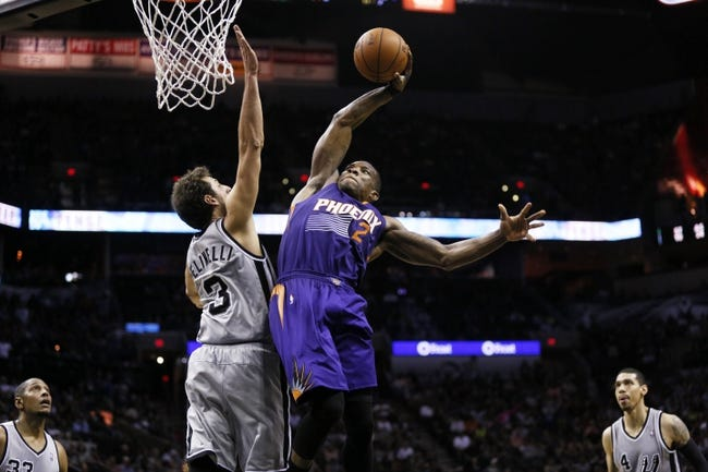 Apr 11, 2014; San Antonio, TX, USA; Phoenix Suns guard Eric Bledsoe (2) dunks over San Antonio Spurs forward Marco Belinelli (3) during the second half at AT&T Center. The Spurs won 112-104. Mandatory Credit: Soobum Im-USA TODAY Sports