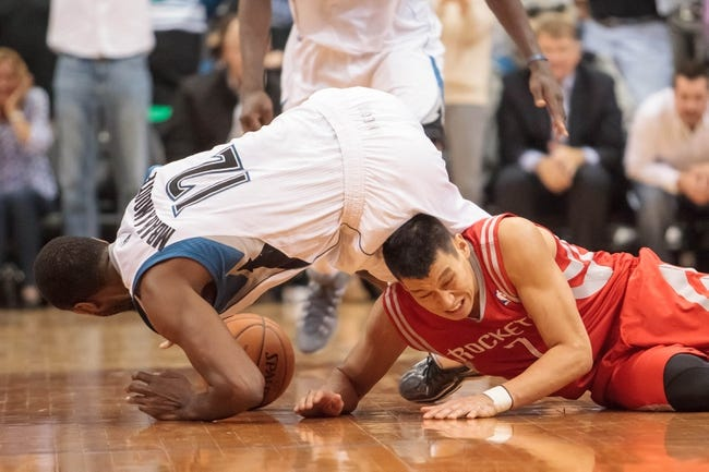 Apr 11, 2014; Minneapolis, MN, USA; Minnesota Timberwolves forward Luc Richard Mbah a Moute (12) and Houston Rockets guard Jeremy Lin (7) dive for a loose ball in the fourth quarter at Target Center. The Minnesota Timberwolves win 112-110. Mandatory Credit: Brad Rempel-USA TODAY Sports